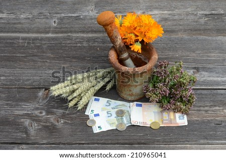 ancient rusty iron mortar and various medical herbs with euro money on old wooden background - stock photo