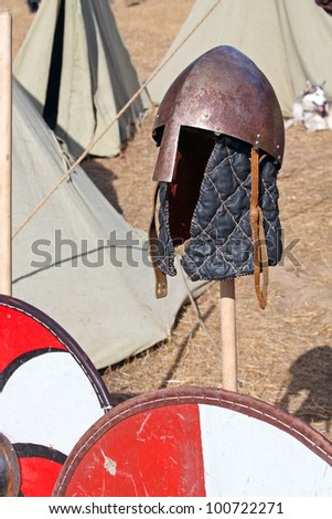 Ancient Scandinavian helmet and shield. Medieval armor pieces - stock photo