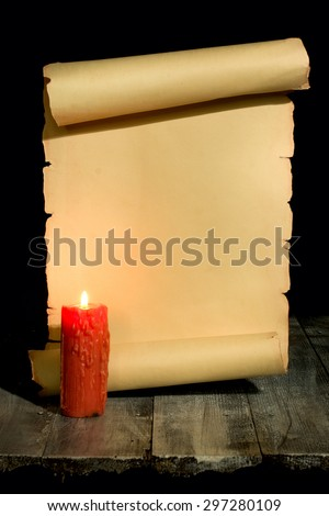 Ancient scroll rolled in wooden Background with Candle - stock photo