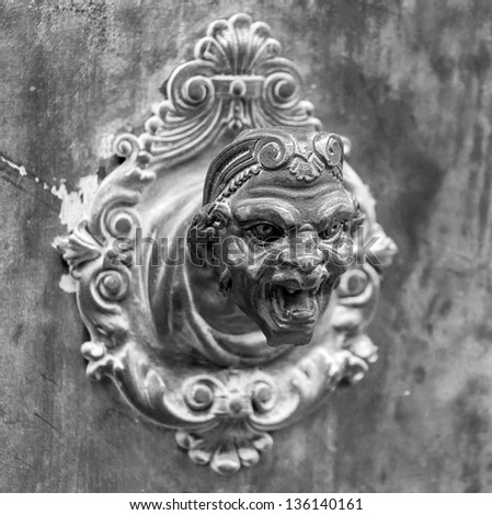Ancient sculpture of a man's head on the wall of a Venetian home - Venice, Italy (black and white)
