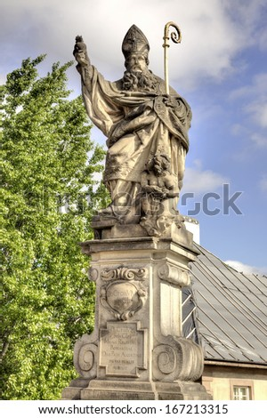 Ancient sculpture on the Charles Bridge. Prague. Blessed St. Augustine tramples heretical books. HDR - stock photo