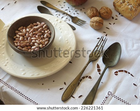 ancient set table with a plate of beans and antique tableware - stock photo