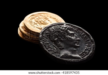Ancient silver an golden coins isolated on black, selective focus, macro - stock photo