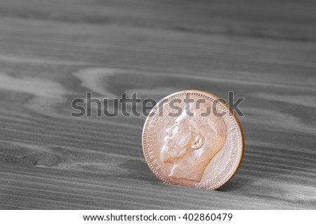 Ancient silver coin on a wooden table - stock photo