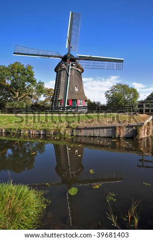 Ancient small village in Holland with windmills and the channel