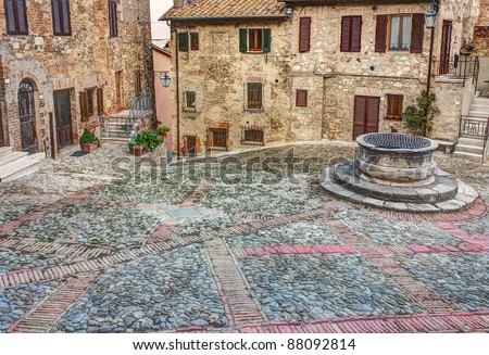 ancient square with water well in the italian old town Castiglione d' Orcia, Tuscany Italy - stock photo