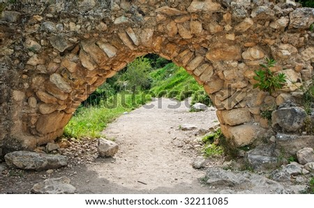 Ancient stone arch on the hiking trail outdoor - stock photo