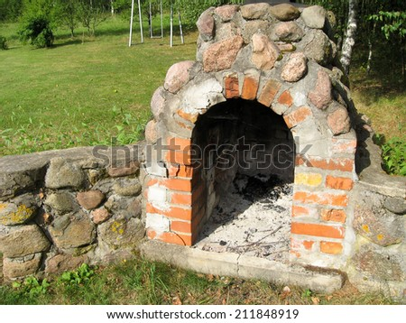 Ancient stone fireplace in the garden during summer. - stock photo