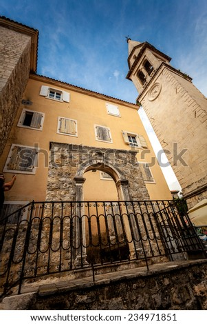 Ancient stone gates and high tower on street of Budva, Montenegro - stock photo