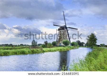 Ancient stone low sail mill near a small canal with dramatic clouds.  - stock photo