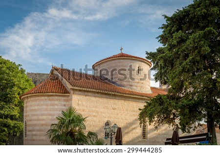 Ancient stone round church with traditional mediterranean red roof. Budva historical center and popular touristic spot. Budva fortress, Montenegro. - stock photo