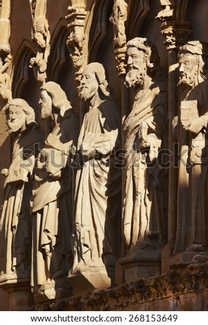 Ancient stone sculptures in a spanish cathedral portico. Olite, Navarra. Vertical - stock photo