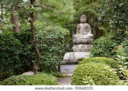 Ancient stone statue of Buddha in a Japanese garden, sitting with legs crossed. - stock photo