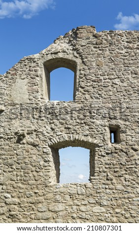 Ancient stone wall of a castle with windows against clear blue sky - stock photo