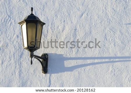 ancient street lamp on a white wall - stock photo