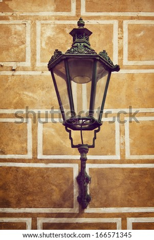 Ancient street lantern lamp on the yellow wall background - stock photo