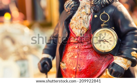Ancient style clock on the statuette of man - stock photo
