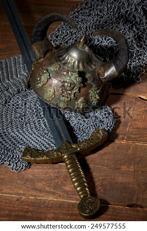 ancient sword, chain armor and the soldier's helmet with horns on a wooden background with beautiful light - stock photo