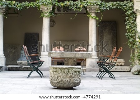 ancient table and chairs with pillars and ivy