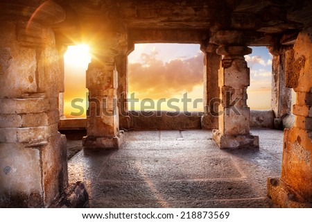 Ancient temple with columns at sunset sky background in India - stock photo