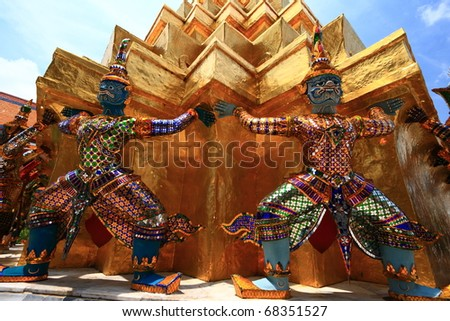 Ancient Thai sacred giants in front of the golden pagoda at the Grand Palace in Bangkok, Thailand. - stock photo