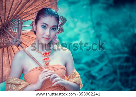 ancient Thai Woman In Traditional dress Of Thailand with vintage umbrella - stock photo
