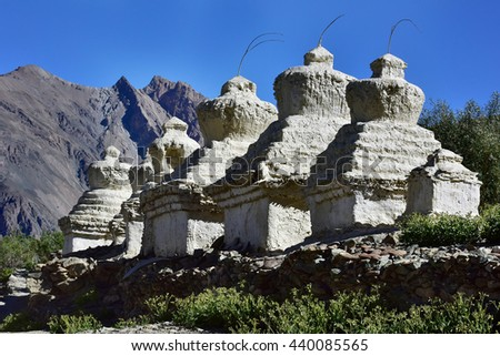 Ancient Tibetan Buddhist white stupa on the hill on a green meadow on a background of high mountains, Stongdey Monastery, Zanskar, Himalayas, Northern India. - stock photo