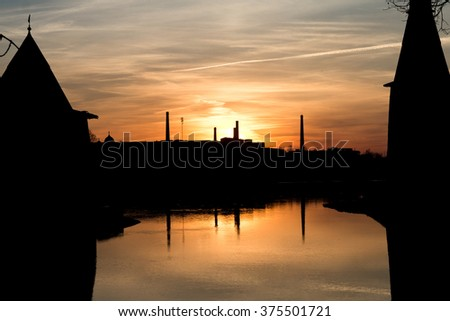 Ancient towers over the river during sunset - stock photo