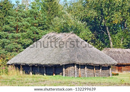 Ancient traditional ukrainian rural barn with a straw roof - stock photo