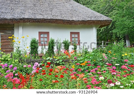 Ancient traditional ukrainian rural hut and flowerbed - stock photo
