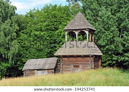 Ancient traditional ukrainian rural wooden barn and church - stock photo