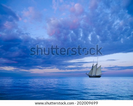 ancient two-mast schooner sailing away to the horizon