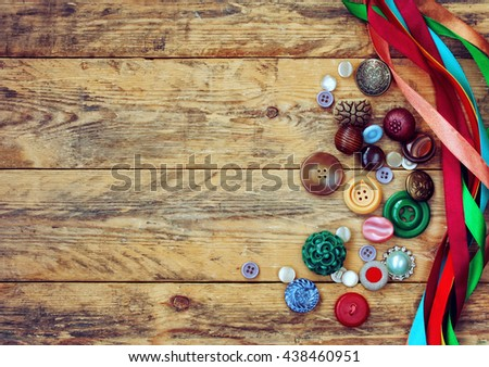 ancient variety buttons and multicolored ribbons lie on wooden table - stock photo