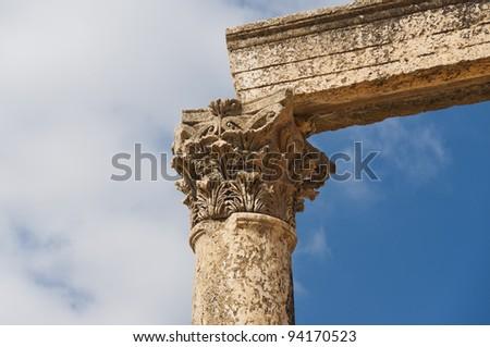 Ancient vertical columns with capitals and lintel along the Roman road in Jerash, Jordan - stock photo