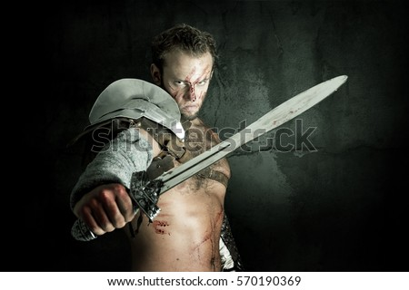 Ancient warrior or Gladiator posing against a dark background with sword