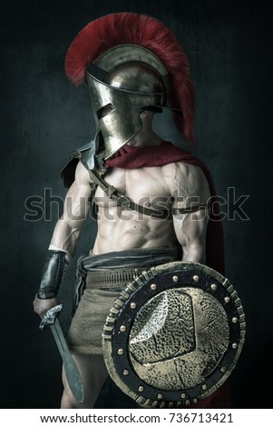 Ancient warrior or Gladiator posing over a dark background