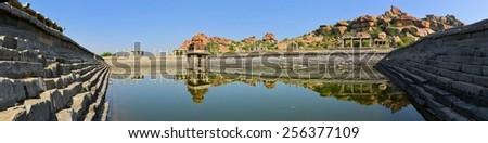 Ancient water pool and temple at Krishna market, Hampi, Karnataka state, India - stock photo