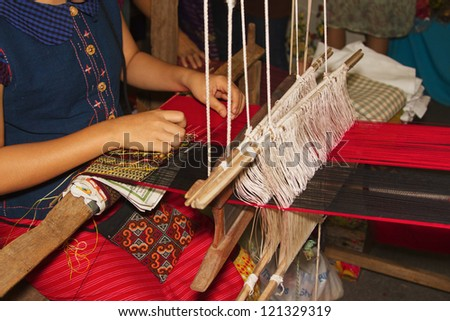 Ancient weaving cloth,Women weaving a cloth  in Chiang Mai - stock photo