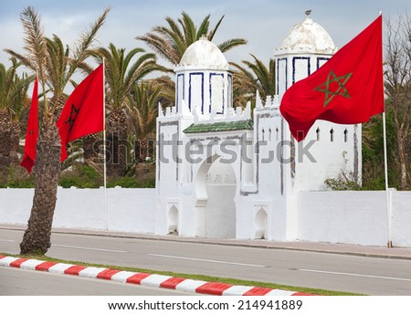 Ancient white gate to the park and flags in Tangier, Morocco - stock photo