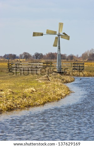 Ancient windmill in the Dutch fields and meadows