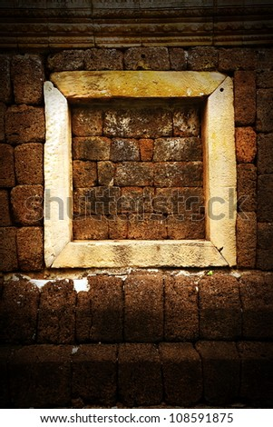 Ancient window in the old stone wall - stock photo