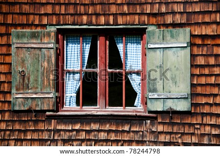 Ancient window on log house wooden wall
