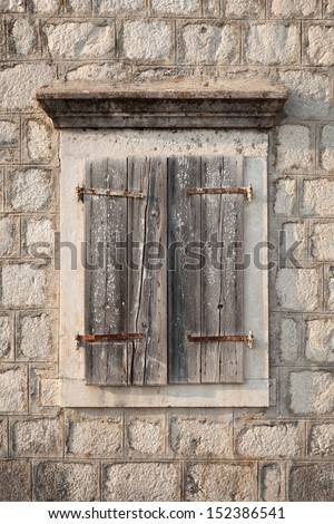 Ancient window with closed wooden jalousies in gray stone wall. Perast town, Montenegro