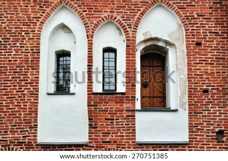 Ancient windows and door on a red brick wall of Saint John Building in Veliky Novgorod - stock photo