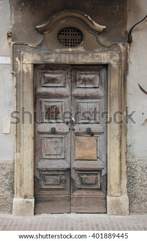 Ancient wood oak door with marble frame portal on old plaster wall, Urbino, Italy