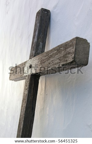 Ancient wooden cross next to a church. - stock photo