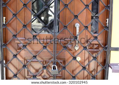 Ancient Wooden Door Behind Grids
