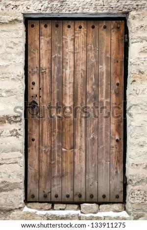 Ancient wooden door in old stone castle wall. Tallinn, Estonia - stock photo