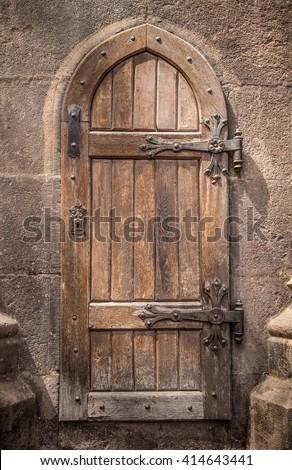 Ancient wooden door in stone castle wall - stock photo
