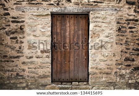 Ancient wooden door in stone castle wall. Tallinn, Estonia - stock photo